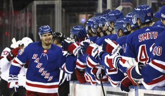 New York Rangers' Pavel Buchnevich, left, is greeted at the bench after scoring a his second goal against the New Jersey Devils during the first period of an NHL hockey game, Saturday, April 17, 2021, in New York. (Bruce Bennett/Pool Photo via AP)