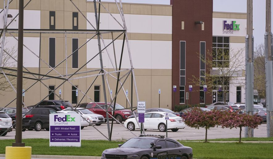 A sheriff's car blocks the entrance to the FedEx facility in Indianapolis, Saturday, April 17, 2021 where eight people were killed during a shooting late Thursday night.   (AP Photo/Michael Conroy)