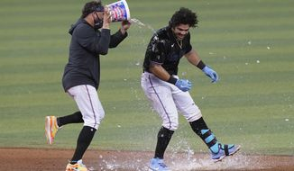 Miami Marlins' Miguel Rojas pours a bucket of water onto Jorge Alfaro after Alfaro hit a double to drive in the winning run in the 10th inning of the team's baseball game against the San Francisco Giants, Saturday, April 17, 2021, in Miami. The Marlins won 7-6. (AP Photo/Marta Lavandier)