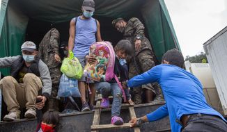 In this Jan. 19, 2021, file photo, a Honduran migrant child is helped off an Army truck after being returned to El Florido, Guatemala, one of the border points between Guatemala and Honduras. The reasons Hondurans continue to flee their country have been well documented: pervasive violence, deep-seated corruption, lack of jobs and widespread destruction from two major hurricanes that struck the region last November. (AP Photo/Oliver de Ros, File)
