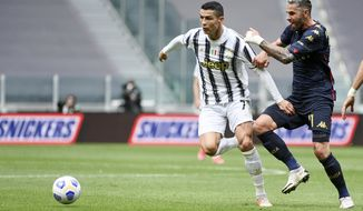 Juventus' Cristiano Ronaldo, right, vies for the ball with Genoa's Valon Behrami during the Serie A soccer match between Juventus and Genoa, at the Turin Allianz stadium, Italy, Sunday, April 11, 2021. (Marco Alpozzi/LaPresse via AP)