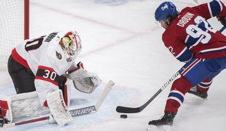Ottawa Senators goaltender Matt Murray, left, stops Montreal Canadiens' Jonathan Drouin during first-period NHL hockey game action in Montreal, Saturday, April 17, 2021. (Graham Hughes/The Canadian Press via AP)