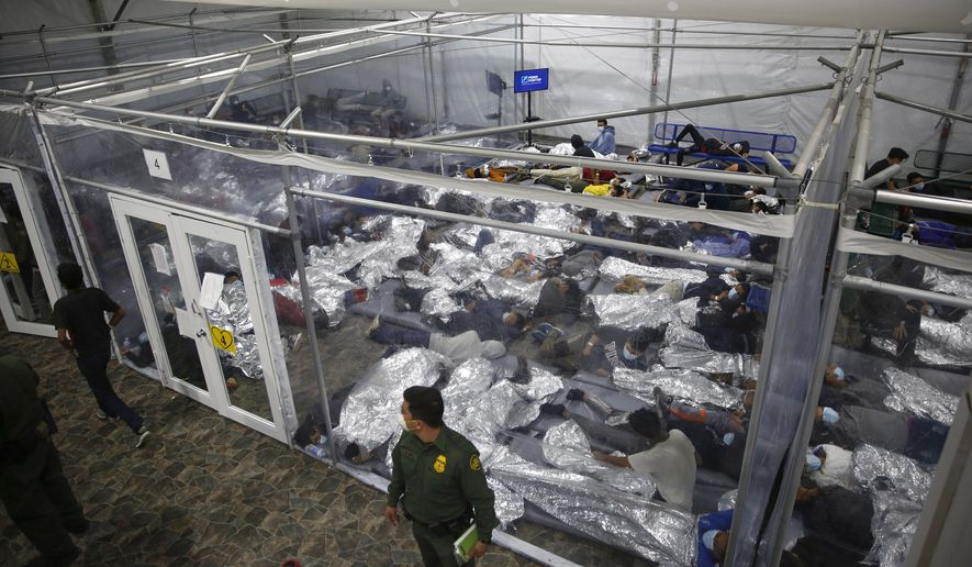 In this March 30, 2021, file photo, young minors lie inside a pod at the Donna Department of Homeland Security holding facility, the main detention center for unaccompanied children in the Rio Grande Valley run by U.S. Customs and Border Protection (CBP), in Donna, Texas. U.S. officials are scrambling to handle a dramatic spike in children crossing the U.S.-Mexico border alone. It's lead to a massive expansion in emergency facilities to house them as more kids arrive than can be released to close relatives in the United States. (AP Photo/Dario Lopez-Mills, Pool, File)