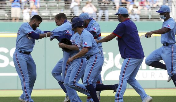 Texas Rangers' Nate Lowe (30) is mobbed by teammates after hitting a walkoff-single that scored Eli White to defeat the Baltimore Orioles in the 10th inning during a baseball game on Sunday, April 18, 2021, in Dallas. (AP Photo/Richard W. Rodriguez)