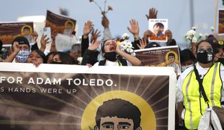Demonstrators attend a peace walk honoring the life of police shooting victim 13-year-old Adam Toledo, Sunday, April 18, 2021, in Chicago's Little Village neighborhood. (AP Photo/Shafkat Anowar)