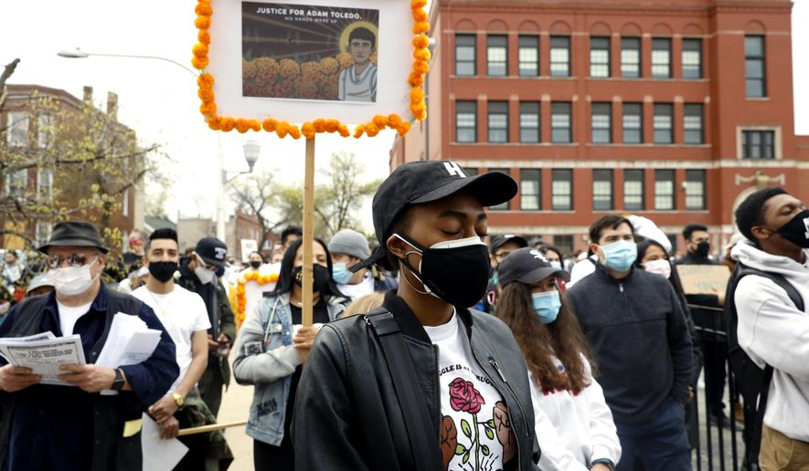 A woman closes her eyes as she participates in a moment of silence during a peace walk honoring the life of police shooting victim 13-year-old Adam Toledo, Sunday, April 18, 2021 in Chicago's Little Village neighborhood. (AP Photo/Shafkat Anowar)