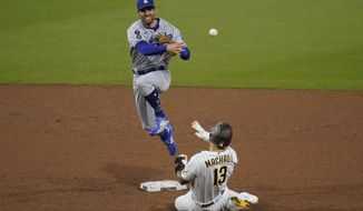 Los Angeles Dodgers second baseman Chris Taylor throws to first for the double play as San Diego Padres' Manny Machado (13) slides in late to second during the sixth inning of a baseball game Saturday, April 17, 2021, in San Diego. Wil Myers was out at first. (AP Photo/Gregory Bull)