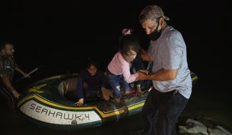 FILE - In this March 30, 2021, file photo, a little girl is helped off an inflatable raft by a church volunteer after being smuggled across the Rio Grande river in Roma, Texas. Roma, a town of 10,000 people with historic buildings and boarded-up storefronts in Texas' Rio Grande Valley, is the latest epicenter of illegal crossings, where growing numbers of families and children are entering the United States to seek asylum. U.S. officials are scrambling to handle a dramatic spike in children crossing the U.S.-Mexico border alone. (AP Photo/Dario Lopez-Mills, File)