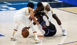 Sacramento Kings guard Delon Wright, center, battles Dallas Mavericks guard Jalen Brunson, left, and forward Tim Hardaway Jr. (11) for a loose ball during the half of a NBA basketball game, Sunday, April 18, 2021, in Dallas. (AP Photo/Brandon Wade)