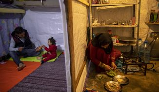 Syrian refugee Ayesha al-Abed, 21, right, prepares food as her Husband Raed Mattar, 24, left, plays with their daughter Rayan, 18 months old, before they break their fast on the first day of fasting month of Ramadan, at an informal refugee camp, in the town of Bhannine in the northern city of Tripoli, Lebanon, Tuesday, April 13, 2021. For many Syrian refugee families in Lebanon, Ramadan comes as a hard life of displacement has gotten even harder after a pandemic year that deepened economic woes in their host country. (AP Photo/Hassan Ammar)
