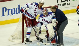 New York Rangers goaltender Alexandar Georgiev, center, is helped off the ice by Pavel Buchnevich, left, and another rangers staff member during the first period of the NHL hockey game against the New Jersey Devils in Newark, N.J., Sunday, April 18, 2021. (AP Photo/Seth Wenig)