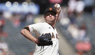 San Francisco Giants pitcher Jake McGee throws to a Cincinnati Reds batter during the ninth inning of a baseball game in San Francisco, Wednesday, April 14, 2021. (AP Photo/Jeff Chiu)