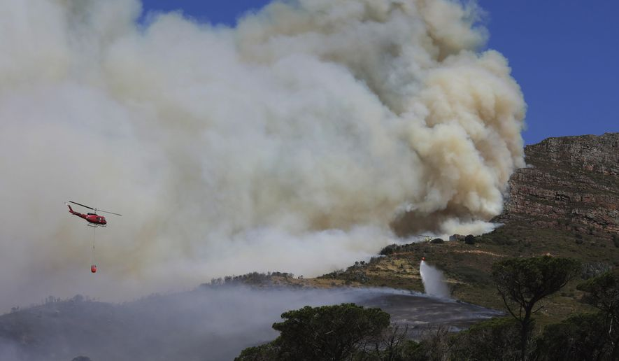 A helicopter drops water over a fire at Rhodes Memorial on Table Mountain, Cape Town, South Africa, Sunday, April 18, 2021. A wildfire raging on the slopes of the mountain forced the evacuation of students from the University of Cape Town. (AP Photo/Nardus Engelbrecht)