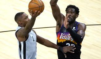 San Antonio Spurs guard Lonnie Walker IV (1) shoots next to Phoenix Suns center Deandre Ayton during the first half of an NBA basketball game Saturday, April 17, 2021, in Phoenix. (AP Photo/Rick Scuteri)