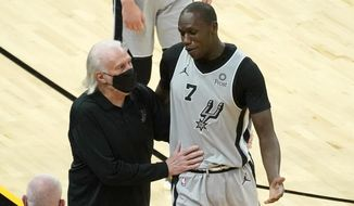 San Antonio Spurs center Gorgui Dieng (7) talks to coach Gregg Popovich after being ejected during the second half of the team's NBA basketball game against the Phoenix Suns, Saturday, April 17, 2021, in Phoenix. (AP Photo/Rick Scuteri)