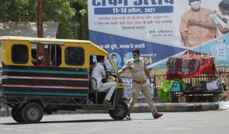 A police man stops an auto rickshaw at a check point during a weekend lockdown to curb the spread of coronavirus in Prayagraj, India, Sunday, April 18, 2021. (AP Photo/Rajesh Kumar Singh)