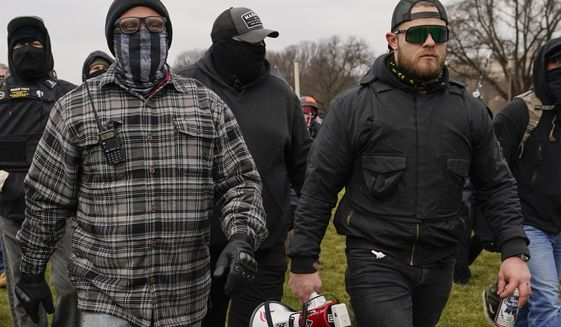 In this Jan. 6, 2021, file photo, Proud Boys members Joseph Biggs, left, and Ethan Nordean, right with megaphone, walk toward the U.S. Capitol in Washington. (AP Photo/Carolyn Kaster, File)