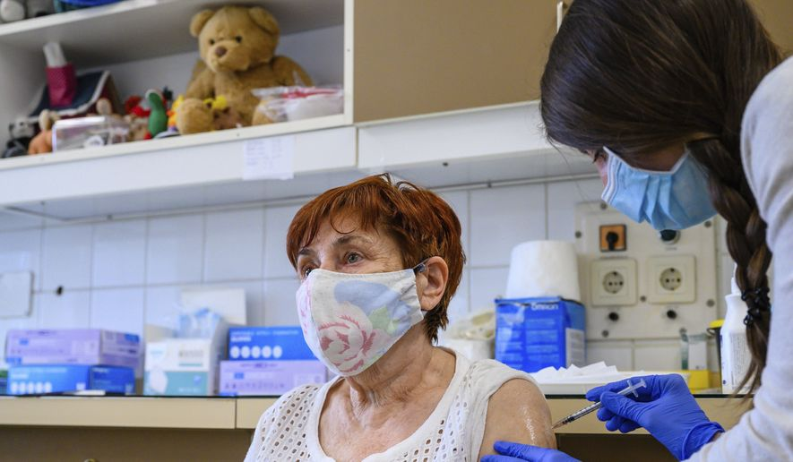 A health worker administers a dose of Pfizer-BioNtech vaccine against the new coronavirus to a patient at Szent Gyorgy Training Hospital in Szekesfehervar, Hungary, Monday, April 19, 2021. (Tamas Vasvari/MTI via AP)