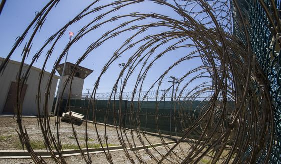 In this Wednesday, April 17, 2019, file photo reviewed by U.S. military officials, the control tower is seen through the razor wire inside the Camp VI detention facility in Guantanamo Bay Naval Base, Cuba. A plan to offer the COVID-19 vaccine to prisoners at the Guantanamo Bay detention center, which was halted earlier in 2021 amid a political backlash, is on again as health authorities on April 19, 2021, expanded the vaccination program on the Navy base in Cuba to the entire adult population of the remote facility. (AP Photo/Alex Brandon, File)