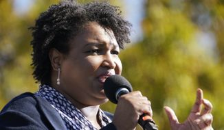 In this Nov. 2, 2020, file photo Stacey Abrams speaks to Biden supporters as they wait for former President Barack Obama to arrive and speak at a rally as he campaigns for Democratic presidential candidate former Vice President Joe Biden at Turner Field in Atlanta. Abrams, Georgia's well-known voting rights advocate, is taking a carefully balanced approach in response to new laws many people have said are an attempt to suppress votes of people of color. When asked about the law changes, she is critical but measured. (AP Photo/Brynn Anderson, File)