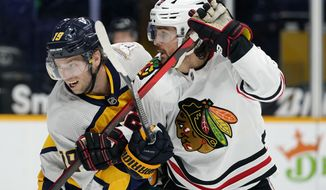 Nashville Predators' Calle Jarnkrok (19) and Chicago Blackhawks' Ryan Carpenter (22) battle for position in the first period of an NHL hockey game Monday, April 19, 2021, in Nashville, Tenn. (AP Photo/Mark Humphrey)