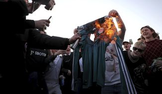 Fans burn a Liverpool replica shirt outside Elland Road, as a protest against Liverpool's decision to be included amongst the clubs attempting to form a new European Super League, in Leeds, England, Monday, April 19, 2021. Reaction to the proposals from 12 clubs to rip up European soccer by forming a breakaway Super League has ranged from anger and condemnation to humor and sarcasm. (Zac Goodwin/PA via AP)