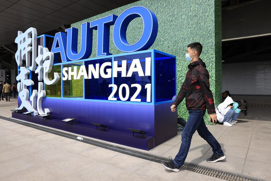 A man wearing a mask passes by a sign ahead of the Auto Shanghai 2021 show in Shanghai on Sunday, April 18, 2021. Automakers from around the world are showcasing their latest products this week in the world's biggest market for auto vehicles. (AP Photo/Ng Han Guan)
