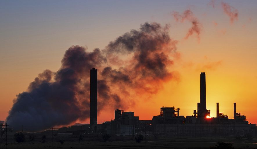In this July 27, 2018, file photo, the Dave Johnson coal-fired power plant is silhouetted against the morning sun in Glenrock, Wyo. More than 300 businesses and investors are calling on the Biden administration to set an ambitious climate change goal that would cut U.S. greenhouse gas emissions by at least 50% below 2005 levels by 2030. (AP Photo/J. David Ake, File)