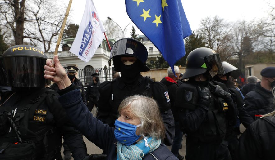 A woman waves a European Union flag in front of the Russian Embassy in Prague, Czech Republic, Sunday, April 18, 2021. (AP Photo/Petr David Josek)