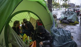FILE - In this March 12, 2020, file photo, people try to stay warm as they face the elements inside a homeless encampment flooded under a rainstorm across the Echo Park Lake in Los Angeles. Faced with an out-of-control homeless crisis, On Monday, April 19, 2021, Los Angeles Mayor Eric Garcetti announced plans to spend nearly $1 billion in the coming year in hopes of getting tens of thousands of unhoused people off the streets. (AP Photo/Damian Dovarganes, File)