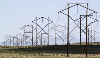 FILE - This May 20, 2012 file photo shows one of the major transmission lines that runs to the west of Albuquerque, N.M. Ahead of hearings that will begin in May 2021, consumer advocacy groups, environmentalists and the New Mexico attorney general's office expressed concerns about a multibillion-dollar merger of the state's largest electric utility with a U.S. subsidiary of global renewable energy giant Iberdrola. (AP Photo/Susan Montoya Bryan, File)