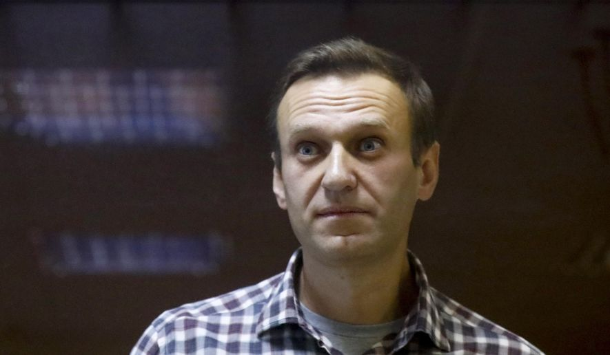 In this Saturday, Feb. 20, 2021, file photo, Russian opposition leader Alexei Navalny stands in a cage in the Babuskinsky District Court in Moscow, Russia. (AP Photo/Alexander Zemlianichenko, File)