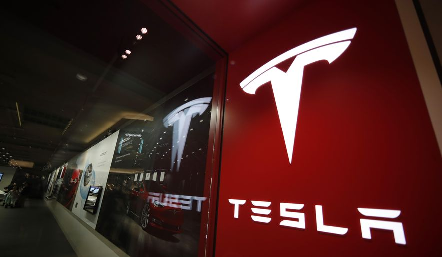This Feb. 9, 2019, file photo shows a sign bearing the company logo outside a Tesla store in Cherry Creek Mall in Denver. Federal safety regulators have sent a team to investigate the fatal crash of a Tesla electric car near Houston in which local authorities say no one was behind the wheel. (AP Photo/David Zalubowski, File)