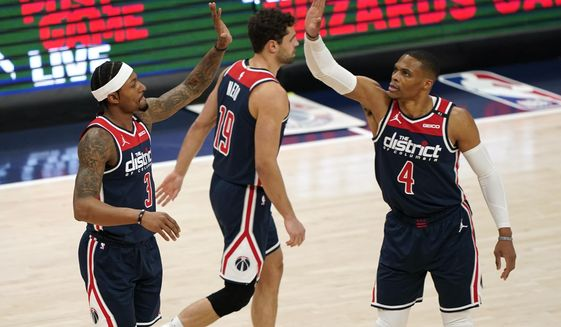 Washington Wizards guard Bradley Beal, left, high-fives teammate Russell Westbrook after Beal was fouled in the first half of an NBA basketball game, Monday, April 19, 2021, in Washington. (AP Photo/Patrick Semansky)