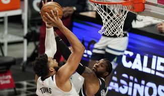 Minnesota Timberwolves center Karl-Anthony Towns, left, shoots as Los Angeles Clippers guard Paul George defends during the first half of an NBA basketball game Sunday, April 18, 2021, in Los Angeles. (AP Photo/Mark J. Terrill)