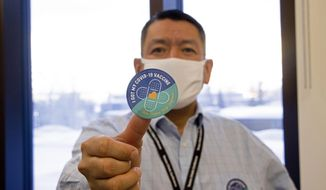 In this undated photo provided by the Tanana Chiefs Conference, shows PJ Simon, chief and chairman of the conference, from Fairbanks, Alaska, displaying a COVID-19 vaccination sticker. Alaska has been one of the leading states in the percentage of its population to be vaccinated against COVID-19. But some of Alaska's highest vaccination rates have been in some of its most remote, hardest-to-access communities, where the toll of past flu or tuberculosis outbreaks hasn't been forgotten. (Rachel Saylor/Tanana Chiefs Conference via AP)