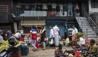 People wearing masks as precaution against the coronavirus shop for vegetables at a Sunday market in Kochi, Kerala state, India, Sunday, April 18, 2021. (AP Photo/R S Iyer)