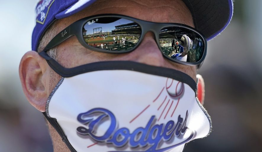 A Los Angeles Dodgers fan wears a team-themed mask as he watches the team play the Seattle Mariners in a baseball game Tuesday, April 20, 2021, in Seattle. (AP Photo/Ted S. Warren)