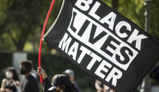 """A man holding a """"Black Lives Matter"""" flag outside of Los Angeles Mayor Garcetti's house after a guilty verdict was announced at the trial of former Minneapolis police Officer Derek Chauvin for the 2020 death of George Floyd, Tuesday, April 20, 2021, in Los Angeles. Former Minneapolis police Officer Derek Chauvin has been convicted of murder and manslaughter in the death of Floyd. (AP Photo/Ringo H.W. Chiu)"""