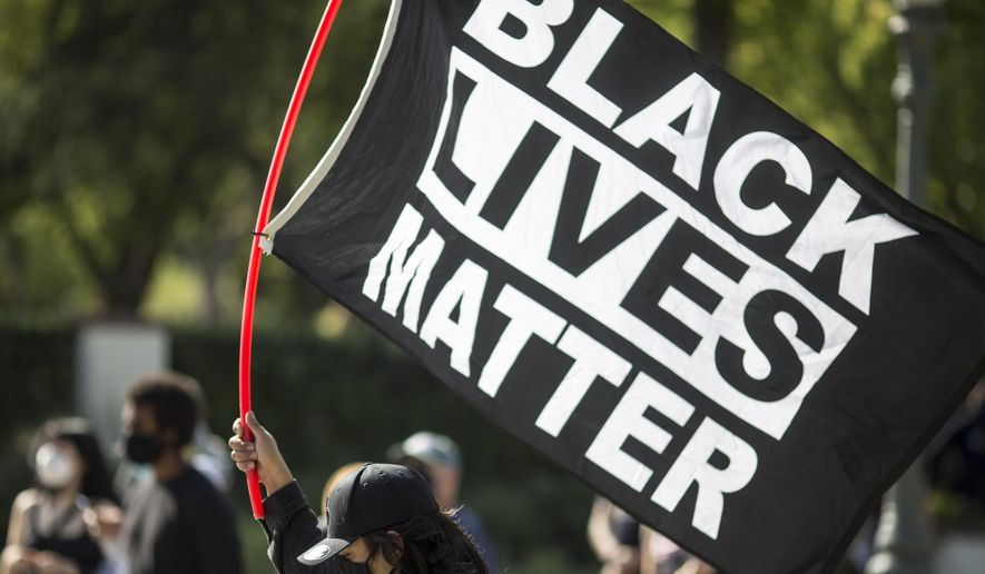 "A man holding a ""Black Lives Matter"" flag outside of Los Angeles Mayor Garcetti's house after a guilty verdict was announced at the trial of former Minneapolis police Officer Derek Chauvin for the 2020 death of George Floyd, Tuesday, April 20, 2021, in Los Angeles. Former Minneapolis police Officer Derek Chauvin has been convicted of murder and manslaughter in the death of Floyd. (AP Photo/Ringo H.W. Chiu)"
