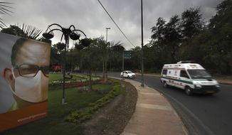 An ambulance carrying a patient drives past a Coronavirus awareness poster on a deserted street on the first day of a six-day lockdown put into place to control the rising cases of coronavirus infections, in New Delhi, India, Tuesday, April 20, 2021. India recorded over 250,000 new infections and over 1,700 deaths in the past 24 hours alone, and the U.K. announced a travel ban on most visitors from the country this week. (AP Photo/Manish Swarup)