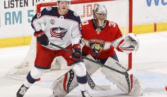 Florida Panthers goaltender Spencer Knight (30) defends the net with Columbus Blue Jackets left wing Eric Robinson (50) waiting for a tip-in attempt during the second period of an NHL hockey game, Tuesday, April 20, 2021, in Sunrise, Fla. (AP Photo/Joel Auerbach)