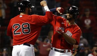 Boston Red Sox's Xander Bogaerts is congratulated by teammate J.D. Martinez after his three-run home run against the Toronto Blue Jays during the fourth inning of a baseball game Tuesday, April 20, 2021, at Fenway Park in Boston. (AP Photo/Winslow Townson)