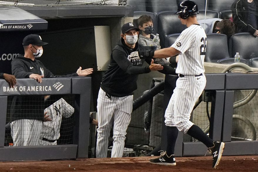 New York Yankees manager Aaron Boone greets DJ LeMahieu (26) at the dugout steps as LeMahieu scored on a bases-loaded walk during the eighth inning of an interleague baseball game against the Atlanta Braves, Tuesday, April 20, 2021, at Yankee Stadium in New York. (AP Photo/Kathy Willens)