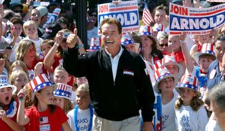 FILE - In this Oct. 5, 2003, file photo, then-Republican candidate for California governor Arnold Schwarzenegger walks up the steps to the state Capitol surrounded by children and waving to supporters during a campaign rally in Sacramento, Calif. No candidate of Schwarzenegger's fame has yet emerged in the expected 2021 recall election against Democratic Gov. Gavin Newsom. (AP Photo/Steve Yeater, File)