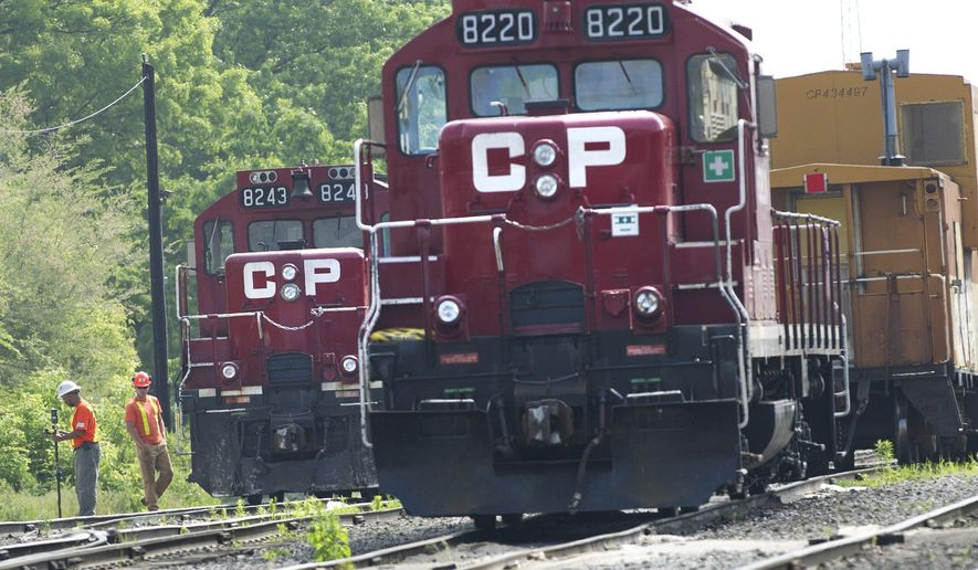 FILE - In this May 23, 2012, file photo, surveyors work next to Canadian Pacific Rail trains which are parked on the train tracks in Toronto. Wary regulators have not approved a major railroad merger since the 1990s, but industry analysts say Canadian Pacific's proposed $25 billion acquisition of Kansas City Southern has a good chance of getting the green light because there is little overlap between the two lines. (Nathan Denette/The Canadian Press via AP, File)