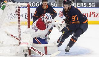 Edmonton Oilers' Connor McDavid (97) is stopped by Montreal Canadiens' goalie Jake Allen (34) during second-period NHL hockey game action in Edmonton, Alberta, Monday, April 19, 2021. (Jason Franson/The Canadian Press via AP)