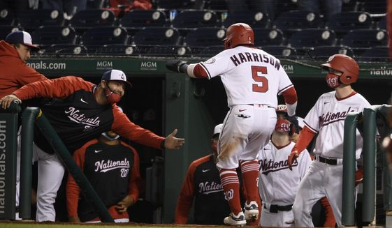 Washington Nationals' Josh Harrison (5) celebrates aat the dugout after he scored from third on a bases-loaded walk to Yan Gomes during the eighth inning of the team's baseball game against the St. Louis Cardinals, Tuesday, April 20, 2021, in Washington. (AP Photo/Nick Wass)
