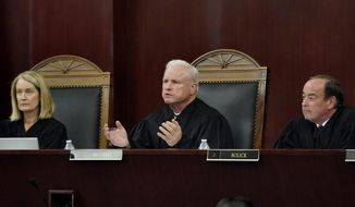 Arizona Supreme Court Chief Justice Robert M. Brutinel, center, speaks during oral arguments, Tuesday, April 20, 2021, in Phoenix as Vice Chief Justice Ann A. Scott Timmer, left, and Justice Clint Bolick listen. The Arizona Supreme Court heard an expedited constitutional challenge to a new voter-approved tax on high-earning Arizonans designed to boost school funding on Tuesday. (AP Photo/Matt York)