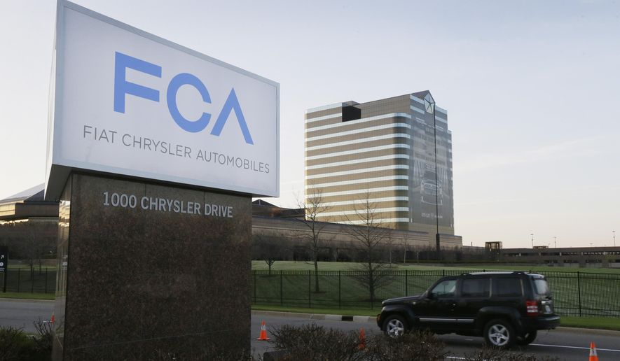 FILE - In this May 6, 2014, file photo, a vehicle moves past a sign outside Fiat Chrysler Automobiles world headquarters in Auburn Hills, Mich. Two Italian managers in Fiat Chrysler's diesel engine program have been indicted by a federal grand jury in Detroit in a widening case alleging a scheme to cheat on U.S. emissions tests. The indictments unsealed Tuesday, April 20, 2021, detail allegations of a plot to dupe the Environmental Protection Agency by rigging more than 100,000 diesel Ram pickup trucks and Jeep SUVs to cheat on EPA tests and exceed pollution limits on real roads. (AP Photo/Carlos Osorio, File)